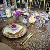 Gold charger, glassware, cutlery and sequin table cloth